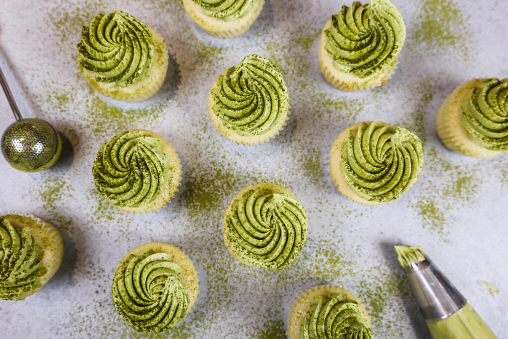 image of matcha cupcakes from overhead that have been frosted with matcha buttercream and dusted with matcha powder