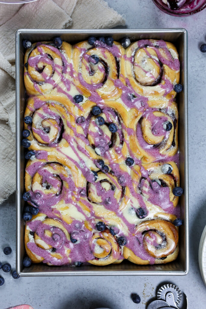 image of blueberry cinnamon rolls that have been baked and drizzled with vanilla and blueberry glaze