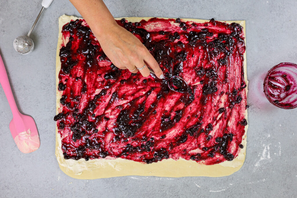 image of blueberry jam being spread onto cinnamon roll dough