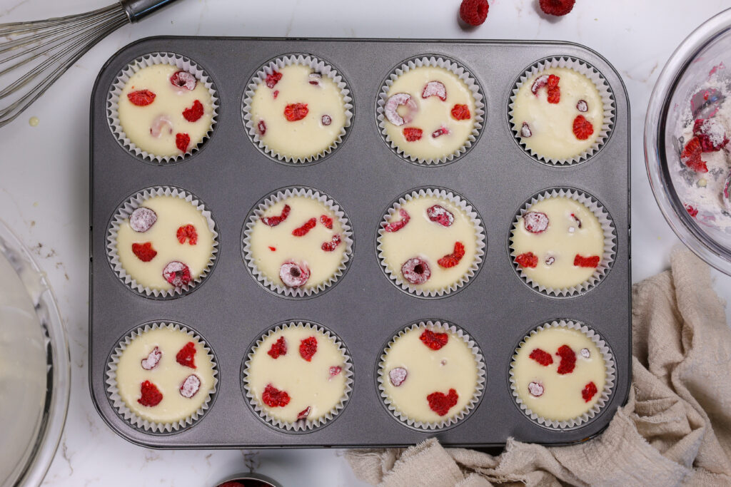 image of raspberry cupcake batter studded with fresh raspberries tossed in flour that're ready to be baked