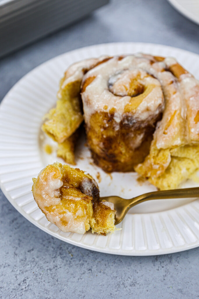 image of a pumpkin pie cinnamon roll that's been cut into to show how soft and tender it is