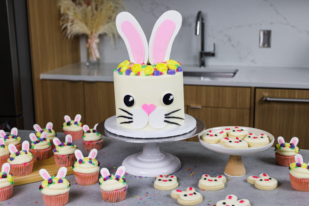 image of a bunny birthday cake made with funfetti cake layers and homemade vanilla buttercream made with matching bunny cookies and cupcakes for a bunny themed party