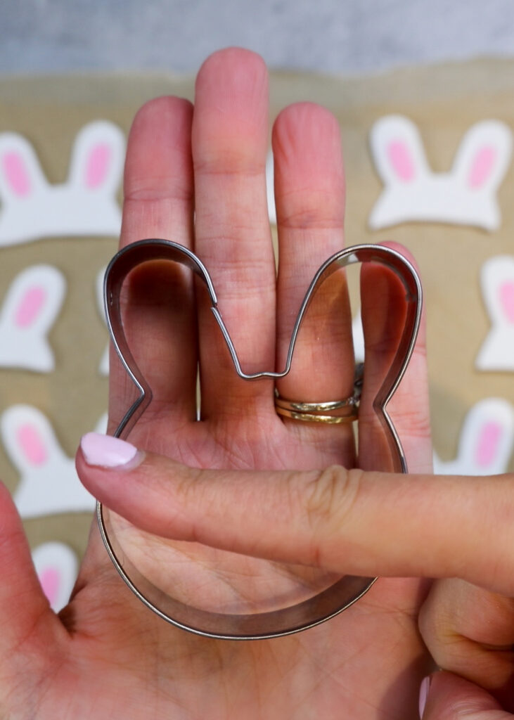 image of a bunny cookie cutter being used as a hack to make bunny ears for some cute bunny rabbit cupcakes
