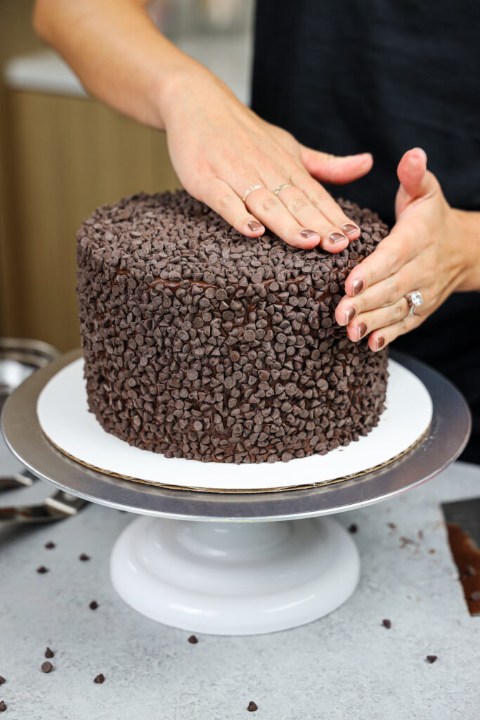 image of a dark chocolate cake being covered with mini chocolate chips