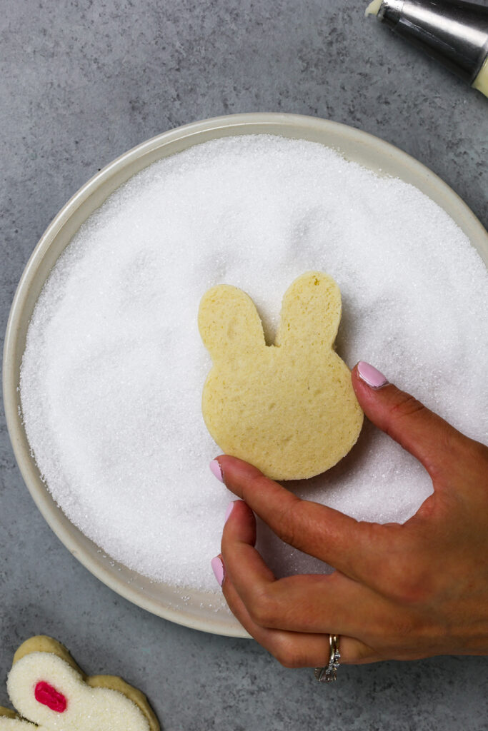 image of a rabbit cookie being dunked in sanding sugar to decorate it