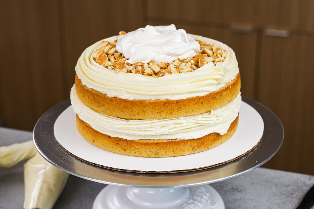 image of a banana layer cake being filled with banana pudding to make a banana pudding layer cake