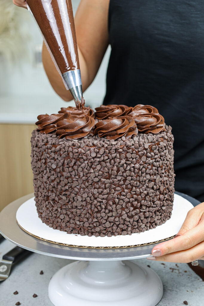 image of chocolate swirls being piped on top a death by chocolate cake