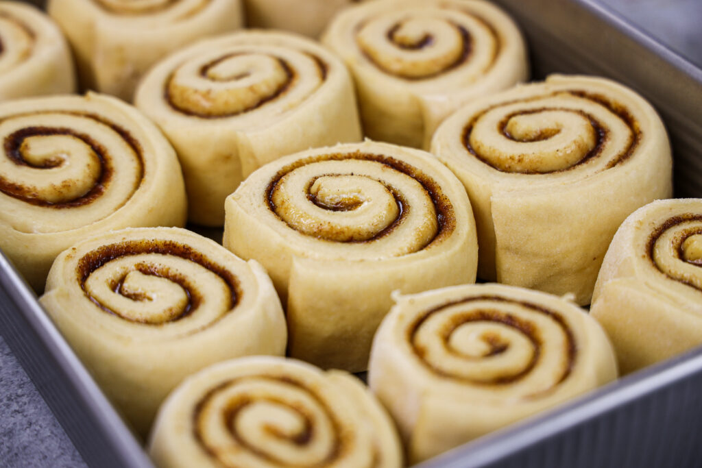 image of pumpkin pie cinnamon rolls that have proofed and are ready to be baked