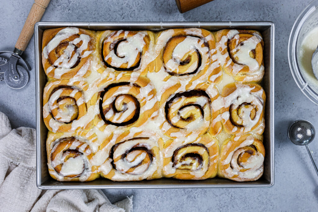 image of pumpkin pie cinnamon rolls that have been baked and glazed with vanilla cinnamon roll glaze