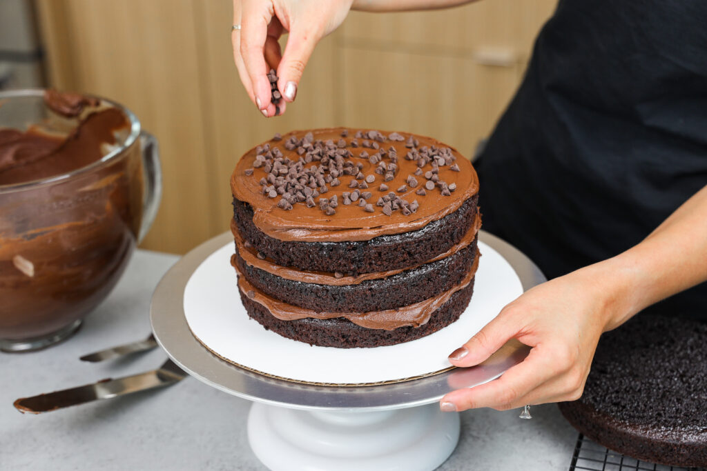image of death by chocolate cake being assembled with dark chocolate frosting and mini chocolate chips