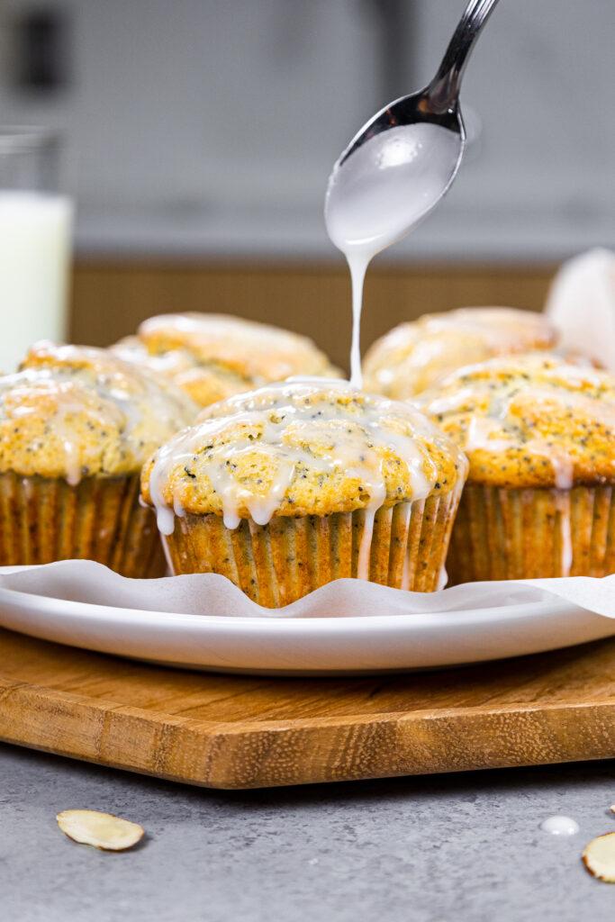 image of almond poppy seed muffins being glazed with almond glaze