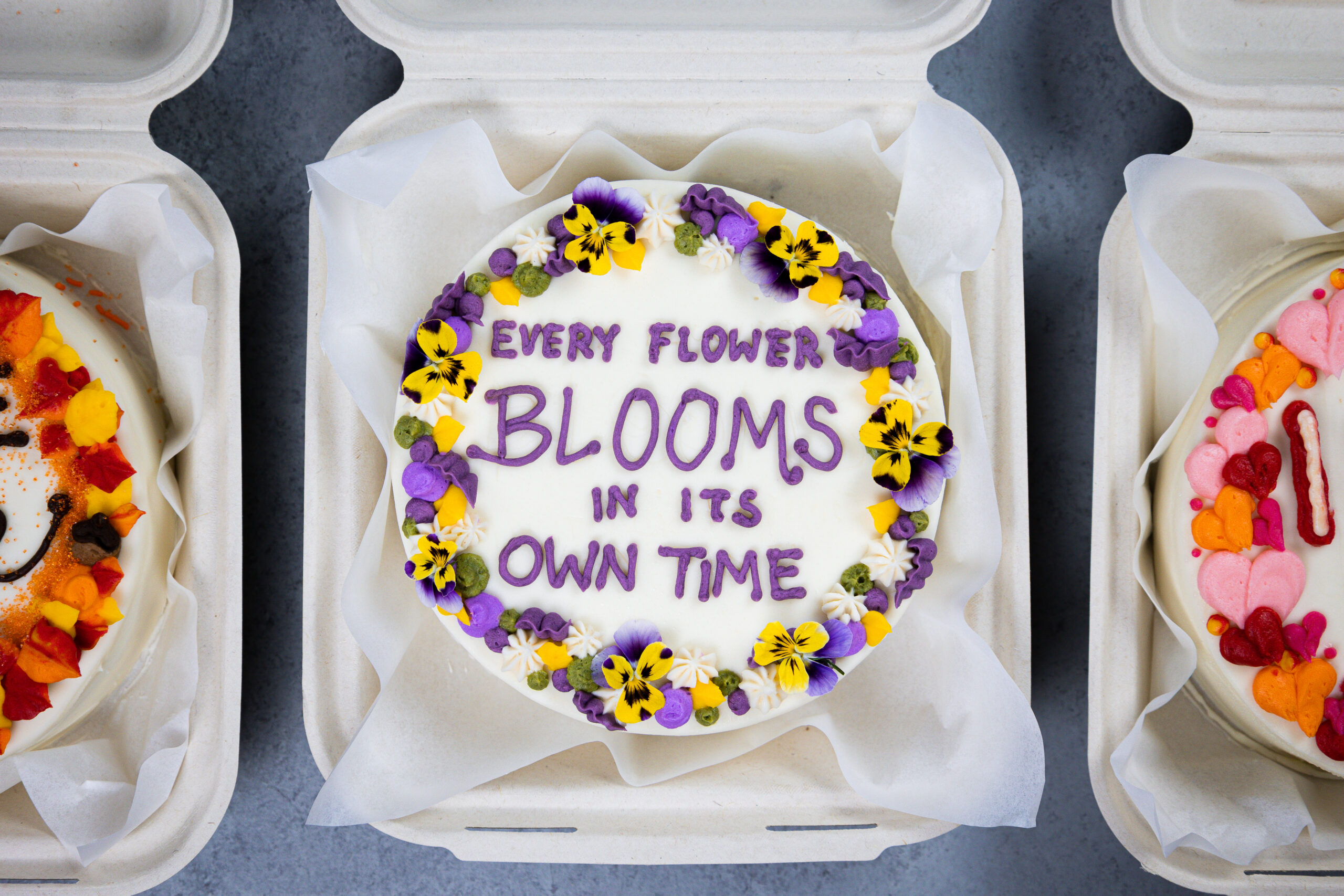 image of an adorable bento cake or lunch box cake decorated with a cute saying and edible flowers