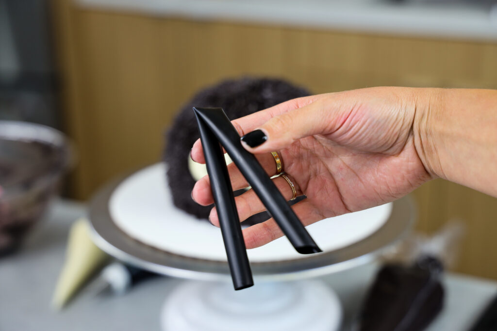 image of a bubble tea straw being bent to make the legs of a spider cake