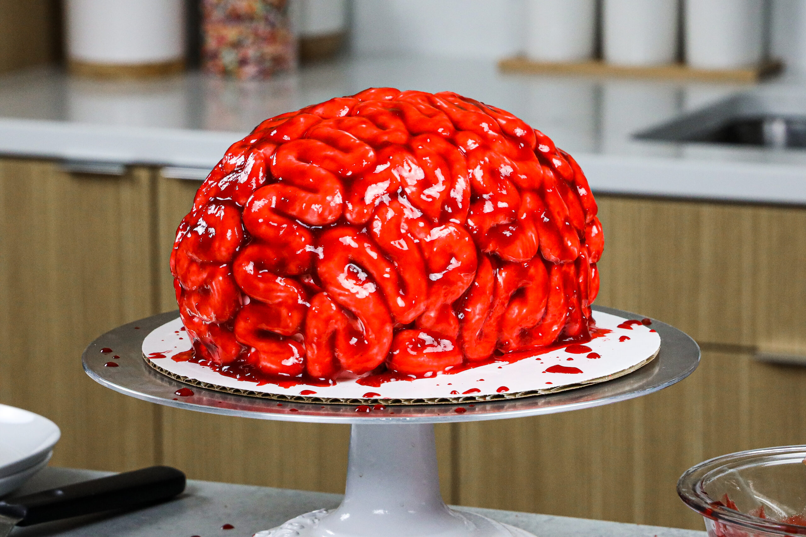 image of a bloody brain cake made for halloween with red velvet cake layers and raspberry jam blood