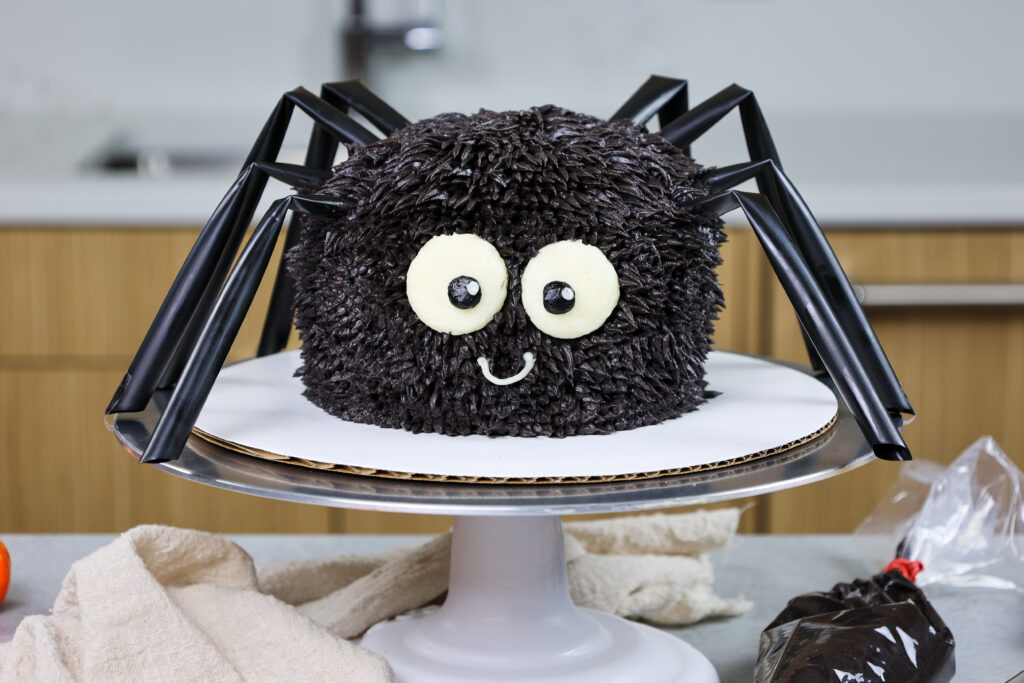 image of a cute and easy spider cake made with buttercream and straw legs