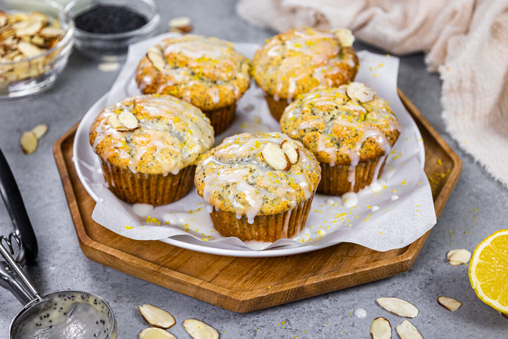 image of almond poppy seed muffins glazed with almond glaze sitting on a tray ready to be eaten