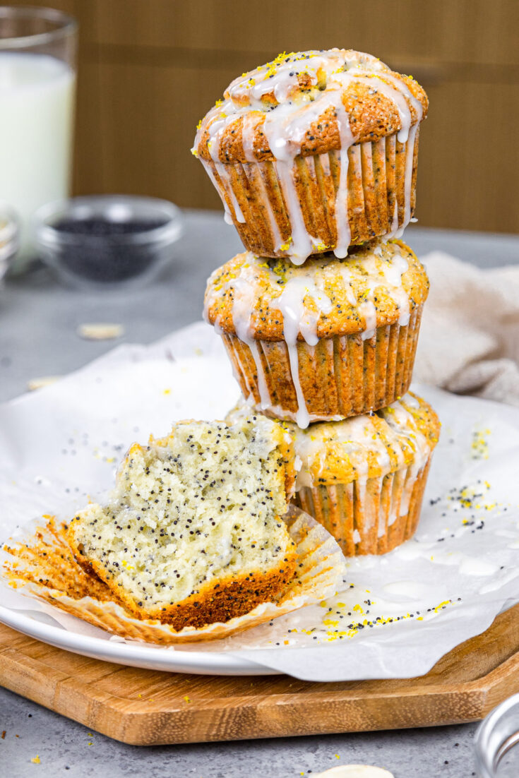 image of almond poppy seed muffins stacked with a muffin cut into to show how tender and soft it is