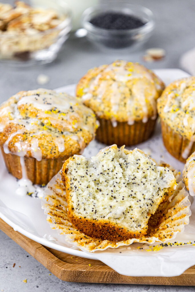 image of almond poppy seed muffins glazed with almond glaze sitting on a tray with one cut open to show how fluffy and tender the inside is