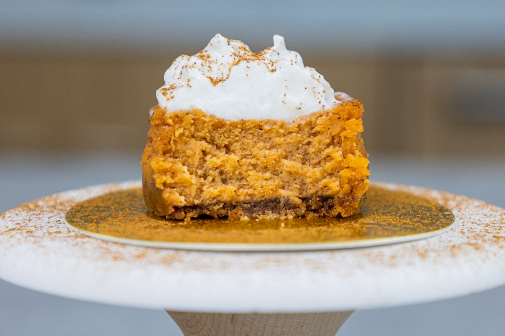 image of a pumpkin cheesecake cupcake that's been cut open to show it's cream inside