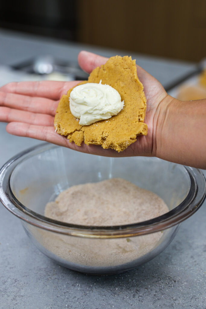image of pumpkin cookie dough that's being filled with cheesecake filling