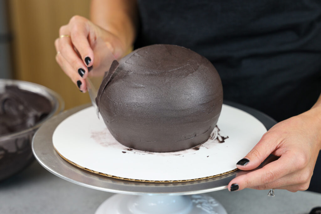 image of black chocolate buttercream being smoothed on a spherical cake