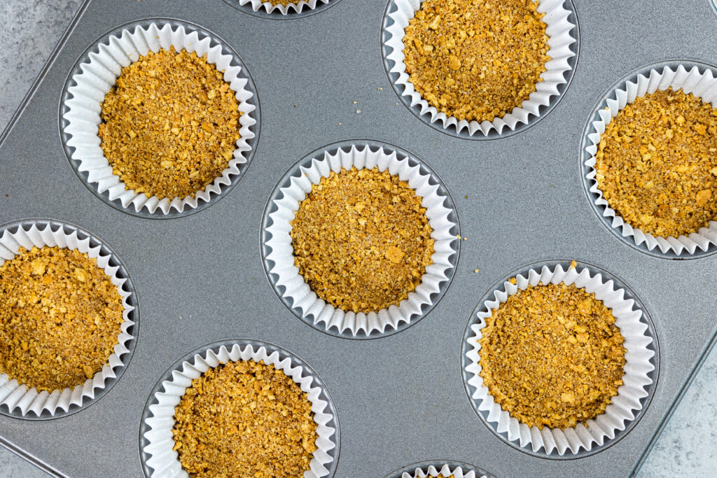 image of a cinnamon graham cracker crust being made in a muffin tin to make mini pumpkin cheesecake