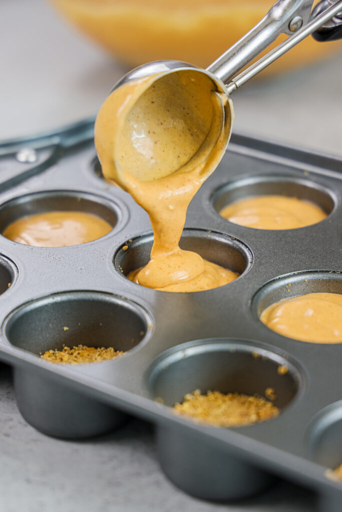 image of a mini cheesecake pan being filled with pumpkin cheesecake batter