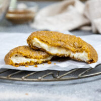 image of a pumpkin cheesecake cookie that's been broken open to show its cheesecake filling