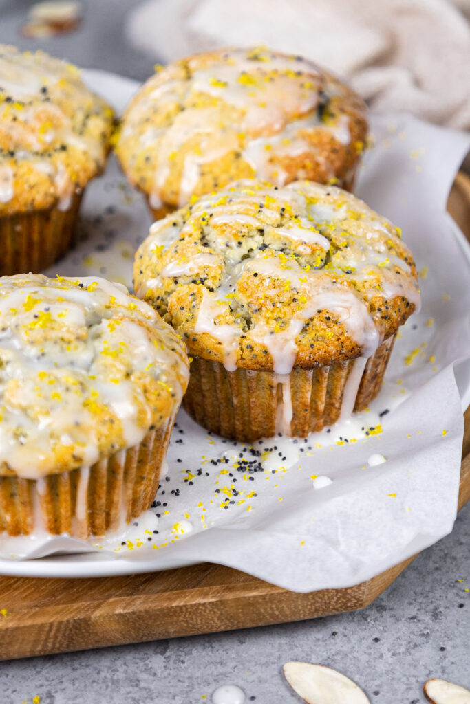 image of almond poppy seed muffins glazed with almond glaze sitting on a tray ready to eat