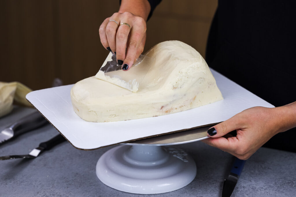 image of cake layers being crumb coated to make a crocodile or alligator cake