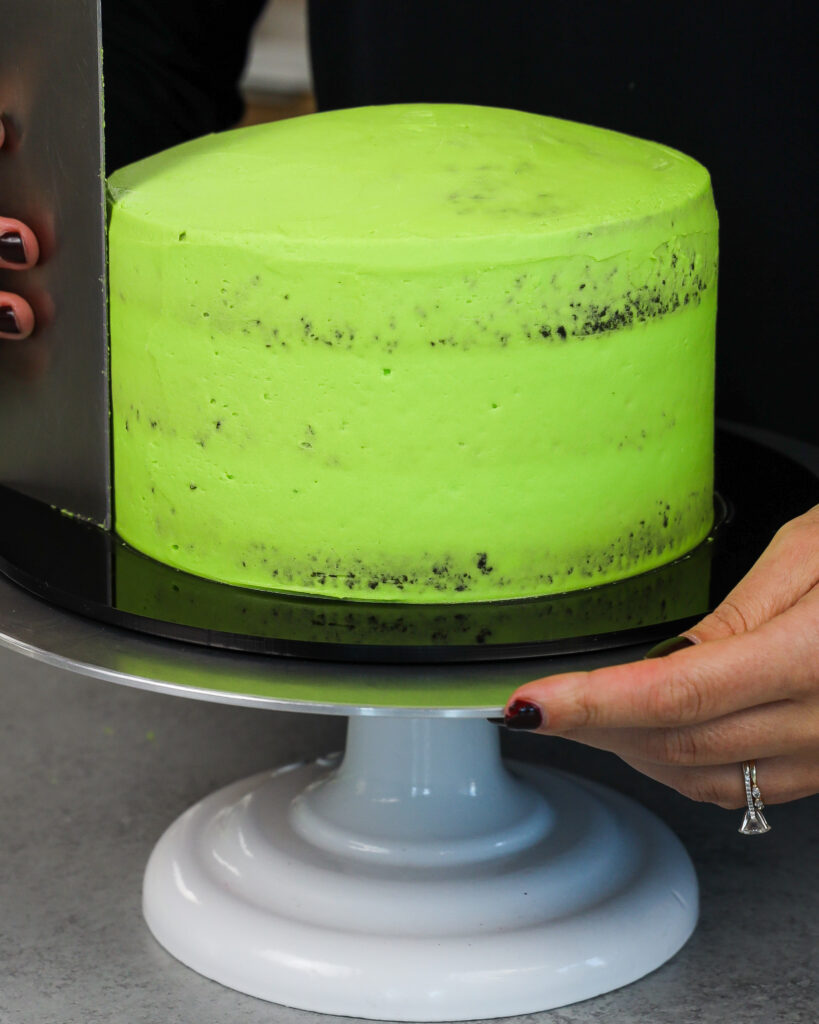 image of a cake being crumb coated in bright green buttercream
