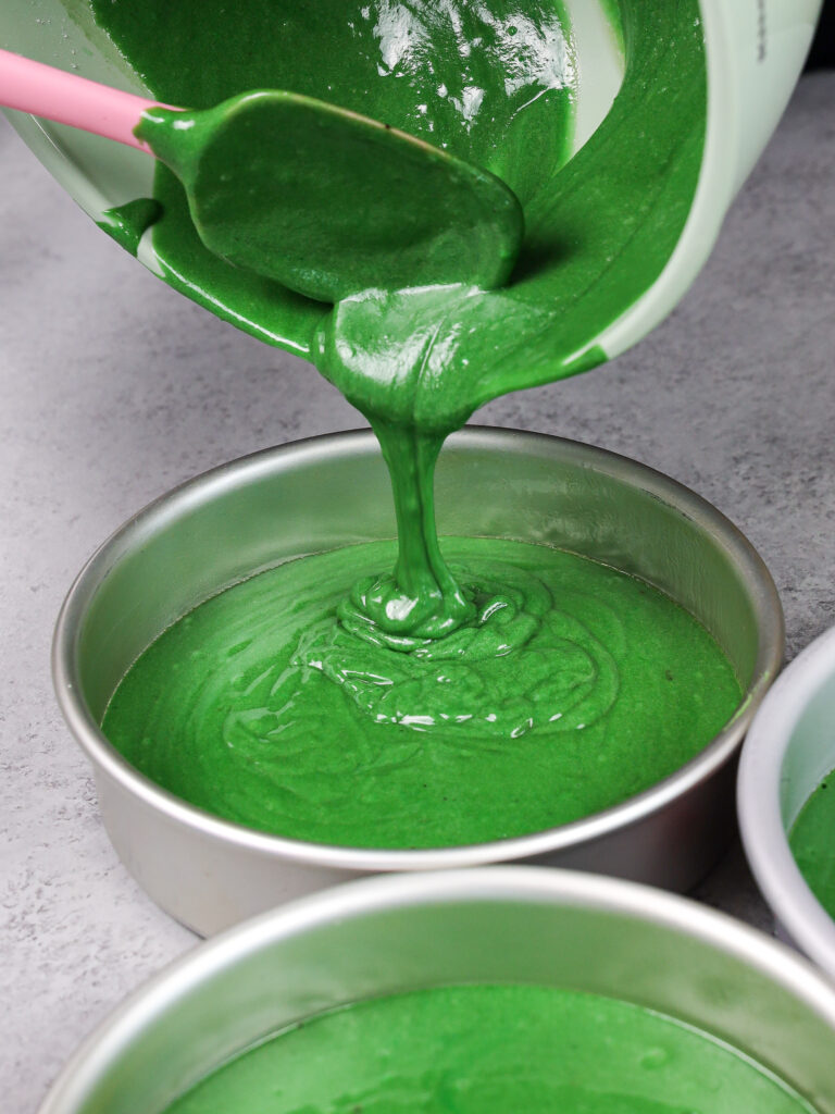 image of green velvet cake batter being poured into a 7 inch cake pan