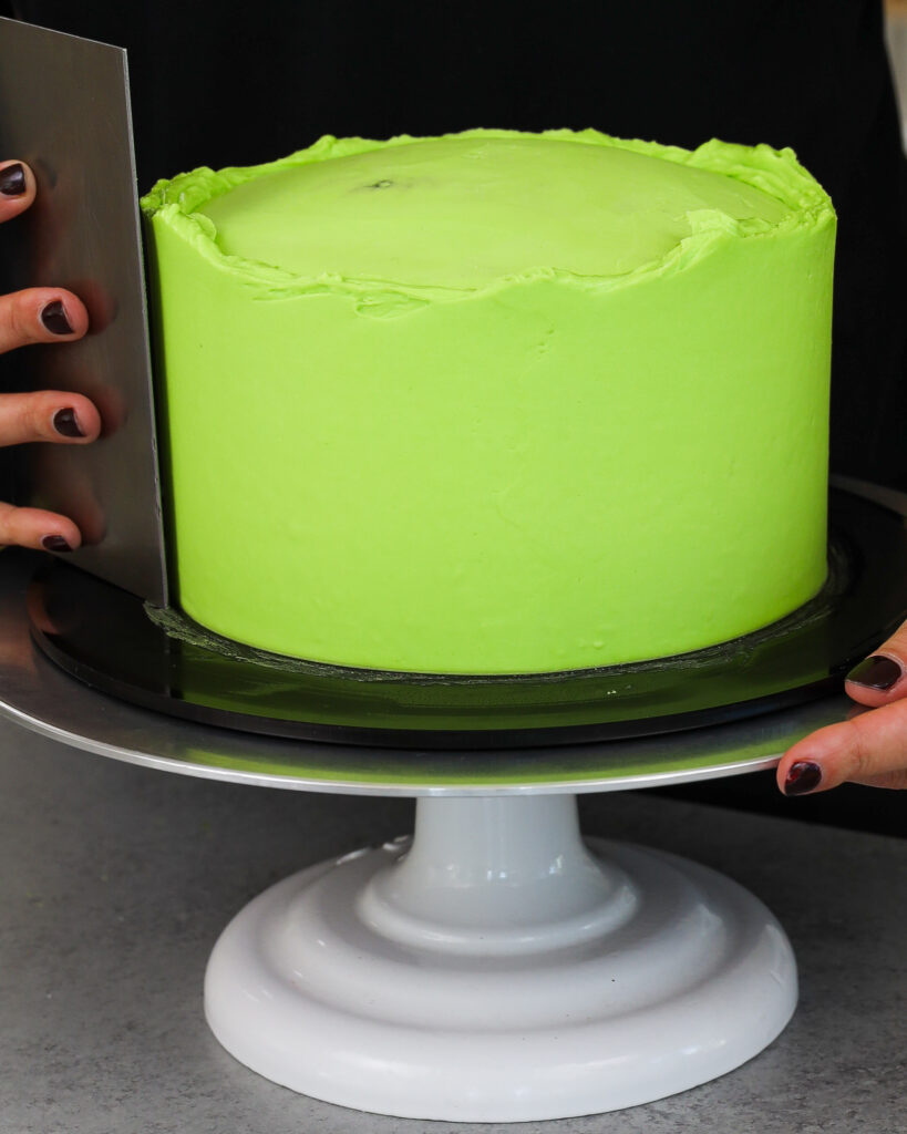 image of a cake being frosted with a second thicker layer of bright green American buttercream